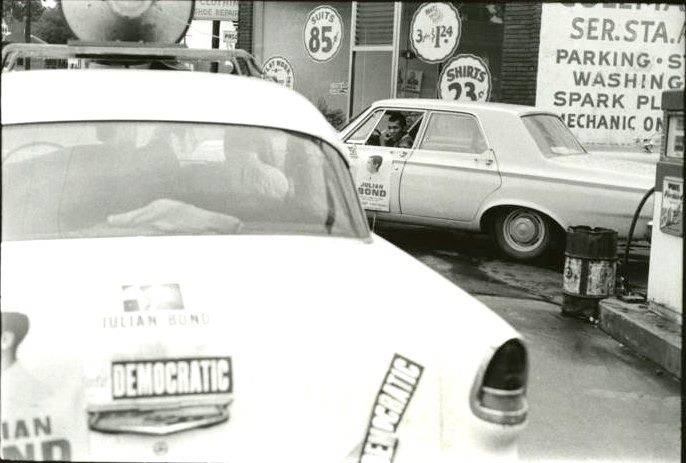Two cars with Democratic bumper stickers sit in a parking lot, Ivanhoe Donaldson is in the driver's seat of the car in the background looking out the window.